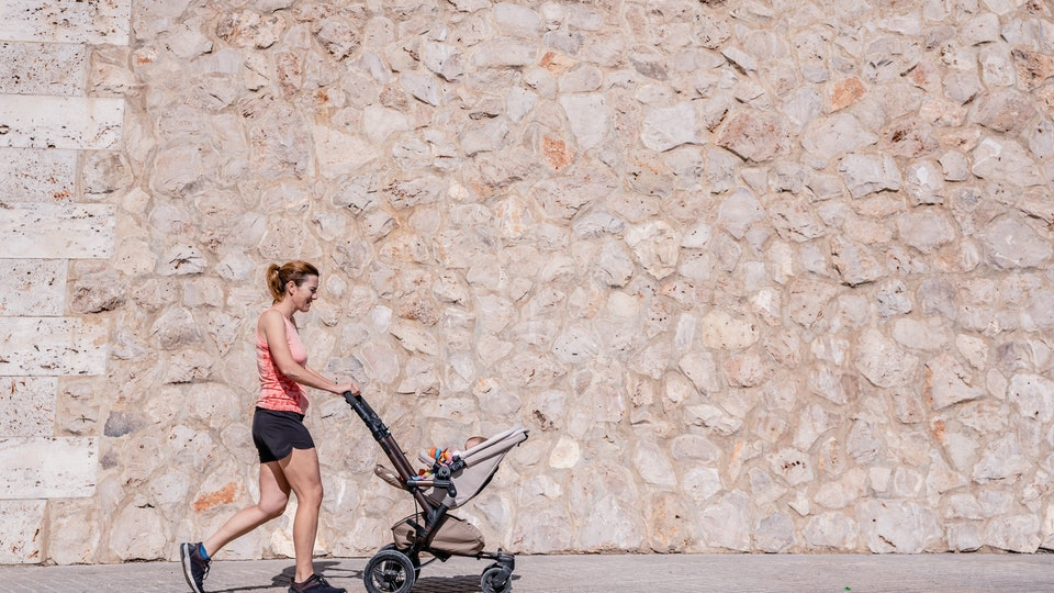 Woman, mother doing fitness pushing the baby stroller.