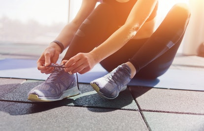Woman tying the laces of sport sneakers sitting on a mat in the gym