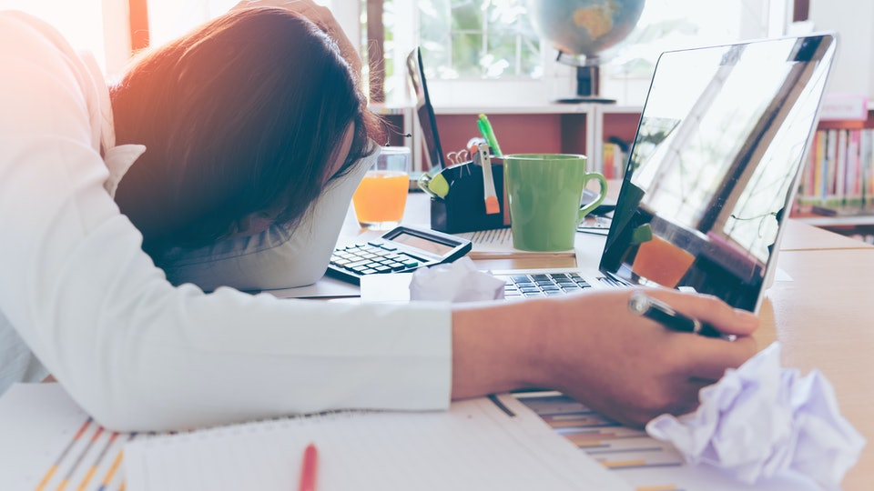 Overworked and tired young woman sleeping on desk