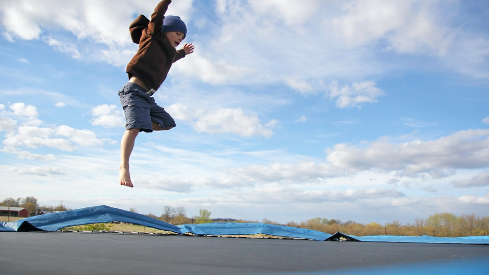 A young child is jumping high while playing outside in the yard on a large, dangerous family trampoline.