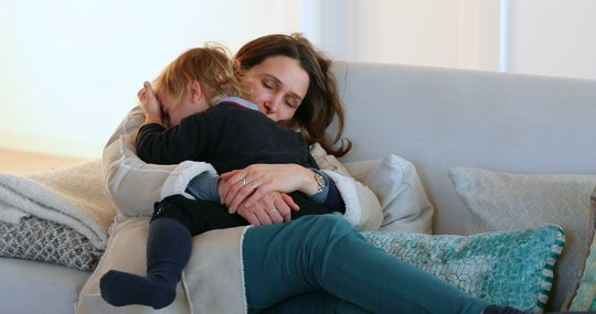 Candid authentic real life family scene with mom and toddler son together in living room sofa about to fall to sleep