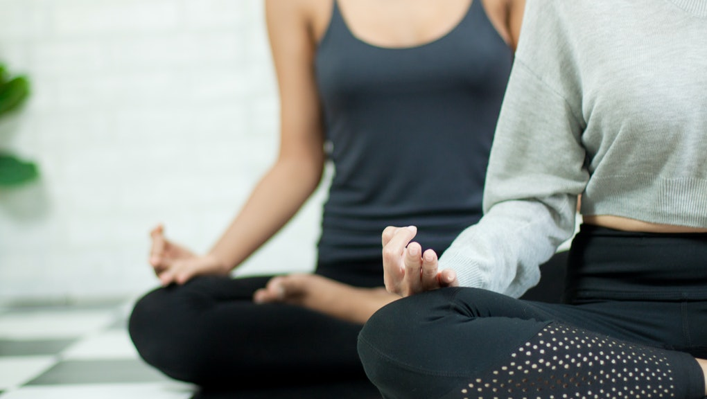 Woman hand in the Yoga exercise and meditation class in healthy plan indoor gym. Female sitting on the floor for training meditation class.
