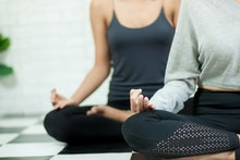 Woman hand in the Yoga exercise and meditation class in healthy plan indoor gym. Female sitting on t...