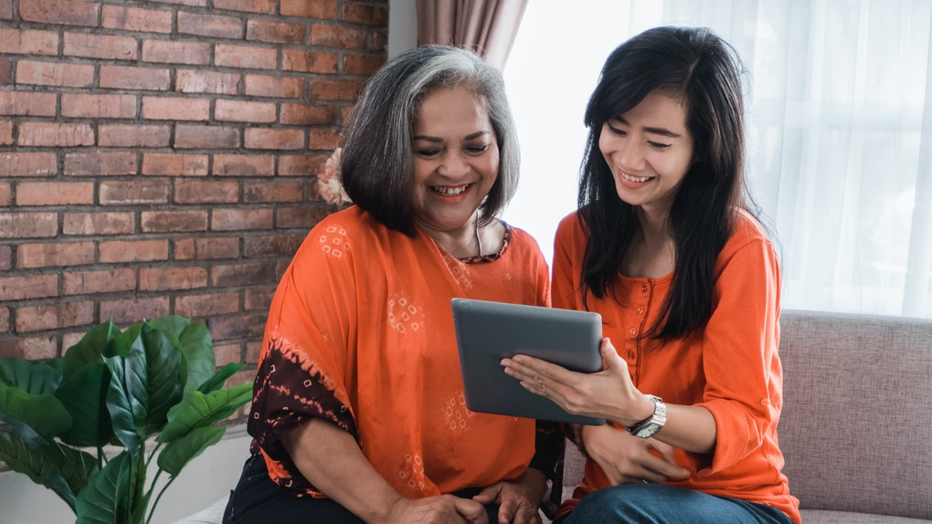 Beautiful senior mom and her adult daughter are using a digital tablet and smiling while sitting on couch at home