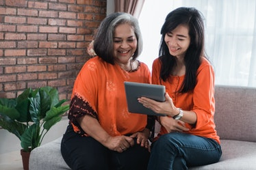 Beautiful senior mom and her adult daughter are using a digital tablet and smiling while sitting on ...