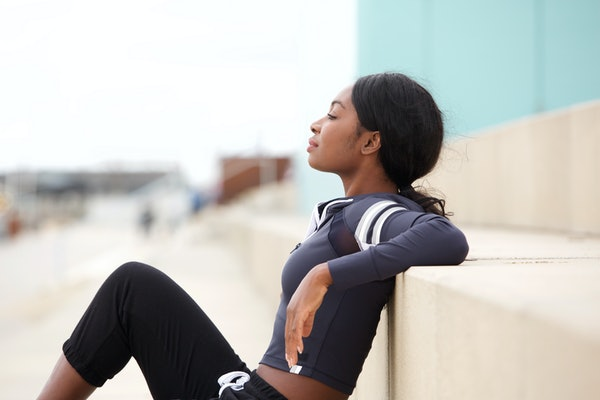 Side portrait of fit young african american sports woman relaxing outside
