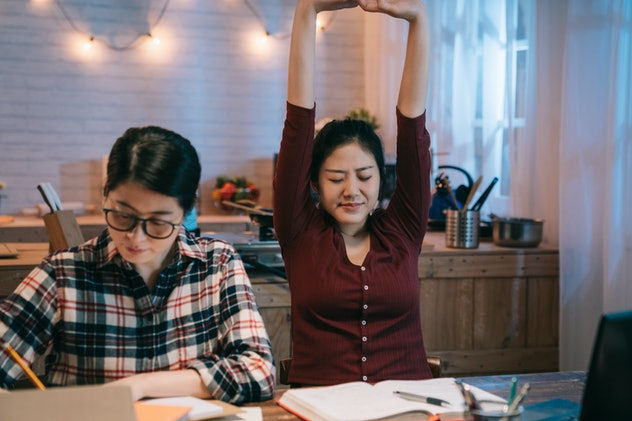 teenage girl student took a nap wake up stretching arms body while her best friend concentrated sitting beside table hardworking doing homework. two women stay up late at night home make project.