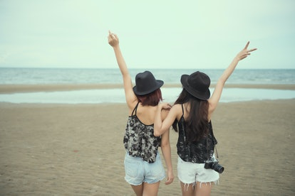 Back view of two woman relax on holiday. Lesbian Couple stand back near sea.Lesbian Couple Together Outdoors Concept. Vintage tone.