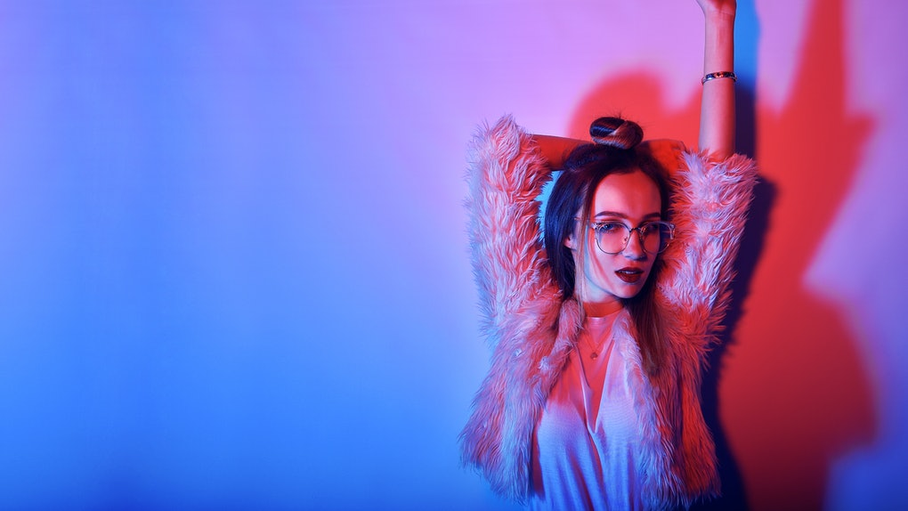 Fashion portrait of young elegant girl in glasses. Colored background, studio shot. Beautiful brunette woman. hipster girl dancing in neon. Woman with stylish hair and red lips