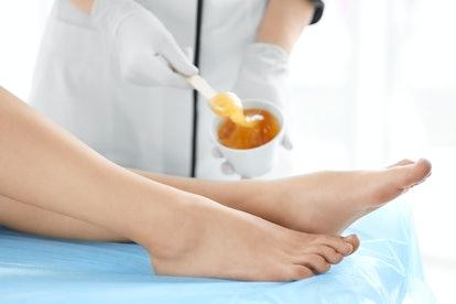 Woman getting wax epilation in salon