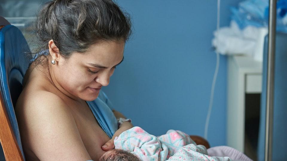 Latina mom breast feeding newborn baby in private hospital