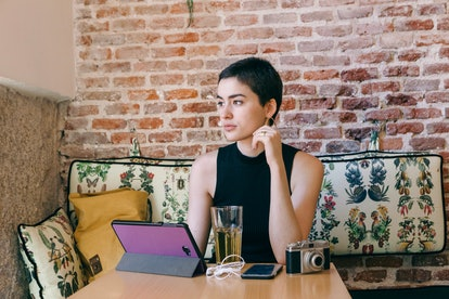 feminist woman using technology at a restaurant