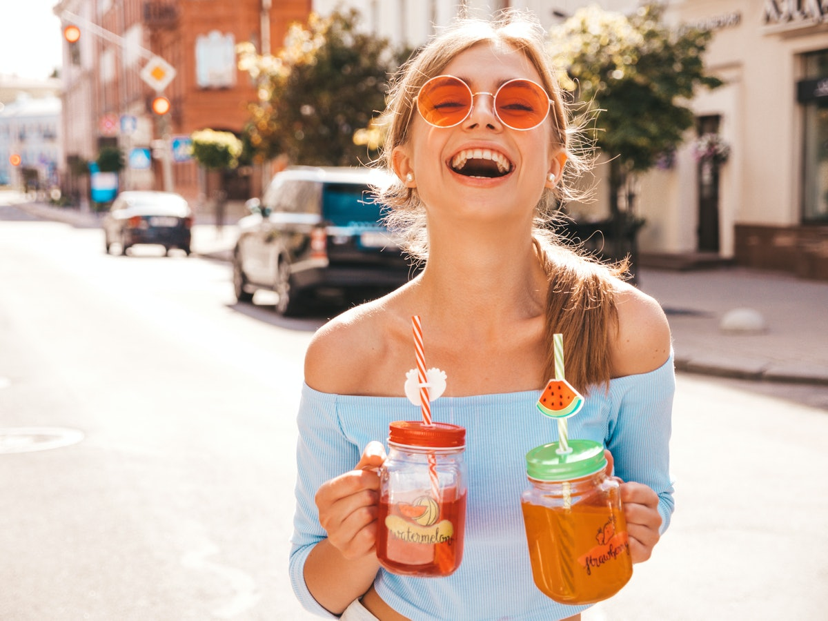 Young beautiful smiling hipster woman in sunglasses.Girl in summer trendy clothes posing in the stre...
