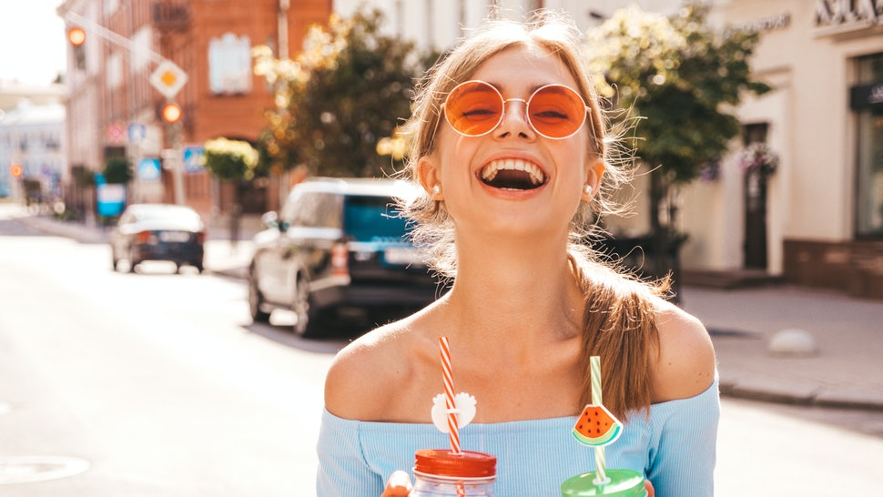 Young beautiful smiling hipster woman in sunglasses.Girl in summer trendy clothes posing in the street.Model holding and drinking two fresh cocktail smoozy drink