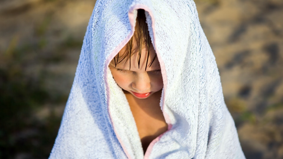 Sad Kid in the Bath Towel on the Summer Beach Portrait closeup