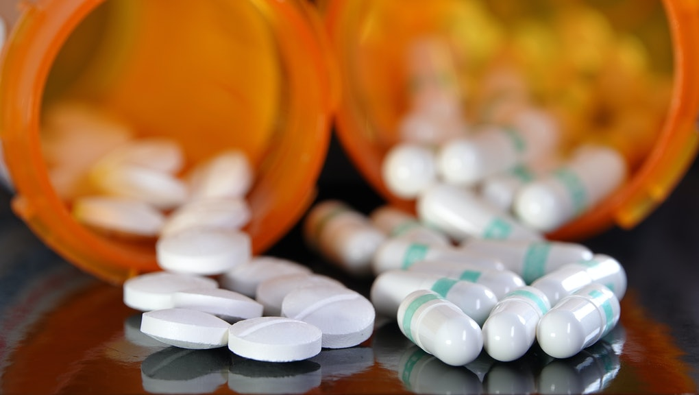 Medication overuse or adverse drug interaction concept - two types of prescription drugs spilling from containers