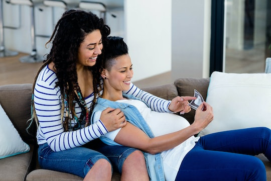 Pregnant lesbian couple sitting on sofa and looking at an ultrasound.