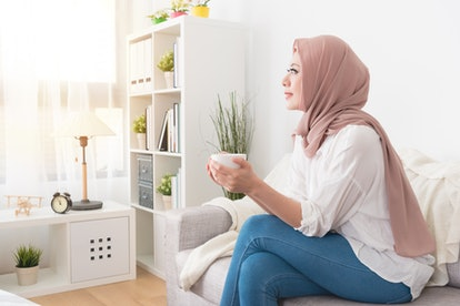 attractive young female muslim holding coffee mug cup sitting on sofa couch and looking at outside daydreaming relaxing enjoying personal afternoon tea time.