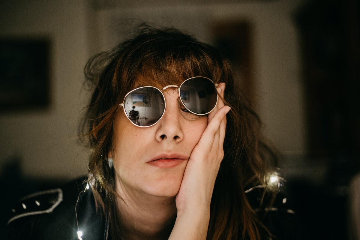 portrait of bored young woman with led lights sunglasses and hand in the face