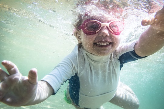 Happy child toddler swimming underwater during summer beach holidays vacation