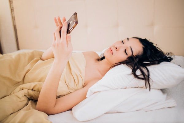 Photo of relaxed woman with black hair watches online story on cell phone, reads post with interesting information in instagram, lies on cozy bed naked covered with quilt.