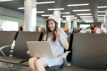 Young traveler tourist woman working on laptop, wave hand for greeting in web-camera during video call wait in lobby hall at airport. Passenger traveling abroad on weekend getaway. Air flight concept