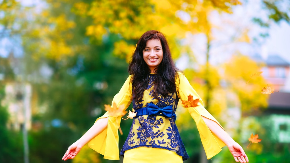 Happy and cheerful girl has a fun with leaves in a fall season. She wears a nice colorful dress. Emotional photo.