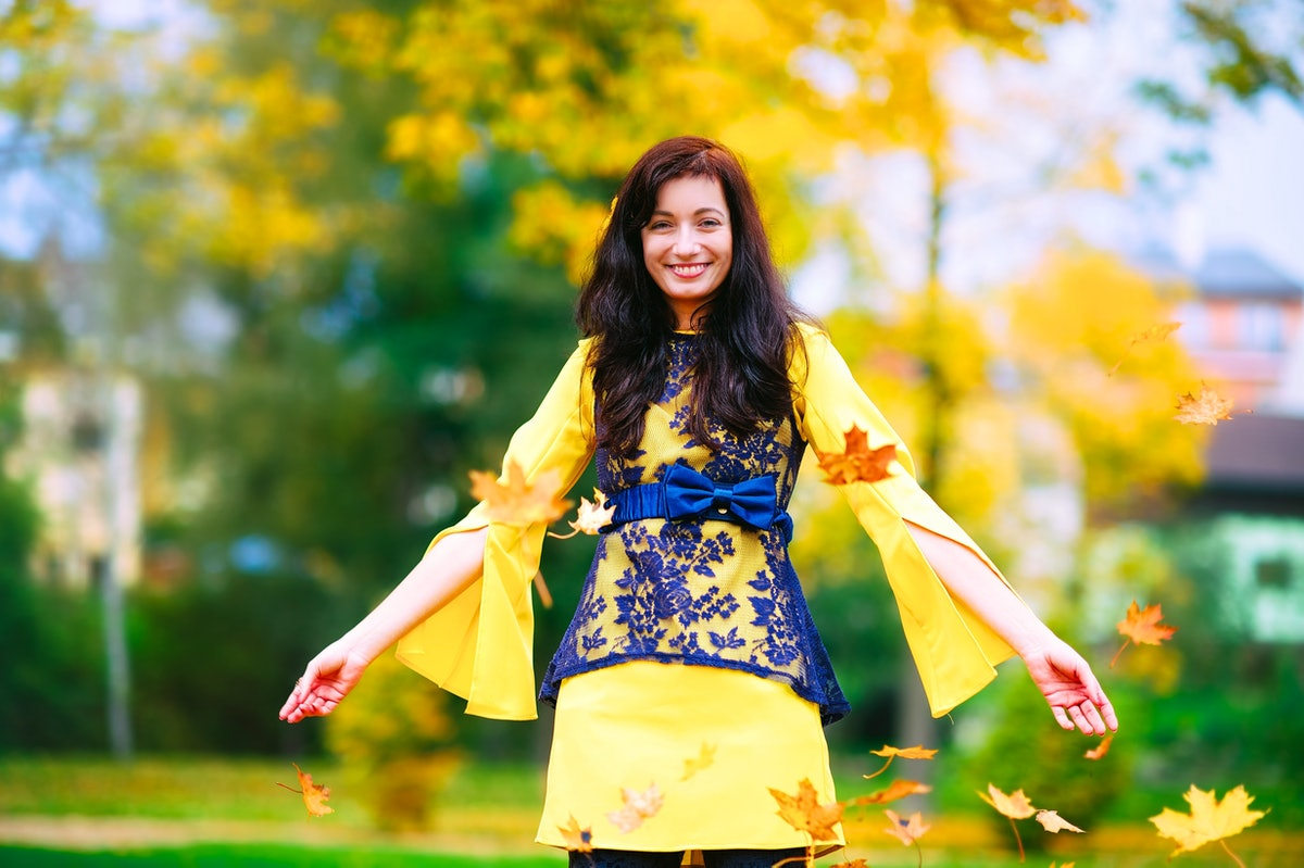 Happy and cheerful girl has a fun with leaves in a fall season. She wears a nice colorful dress. Emo...