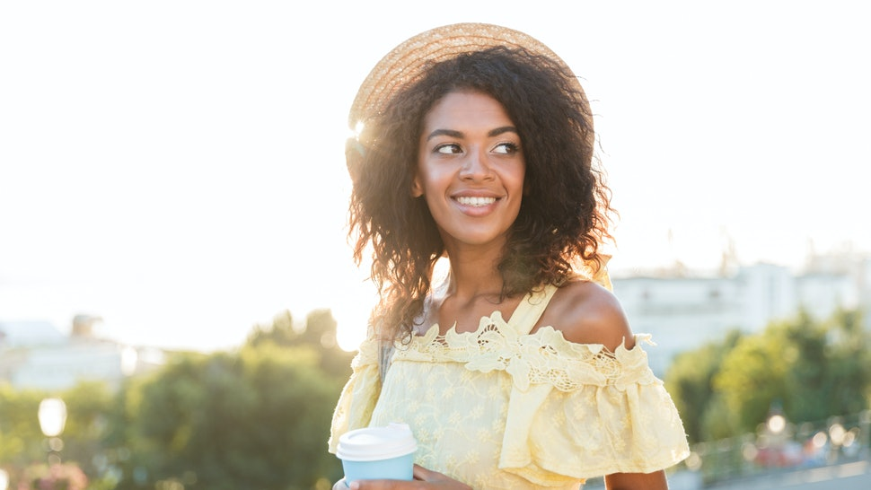 Happy young african woman in summer dress walking at the city, holding cup of coffee