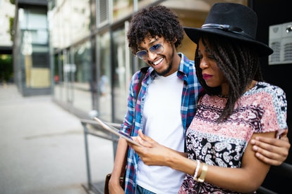 Young attractive african couple talking and looking at digital tablet.