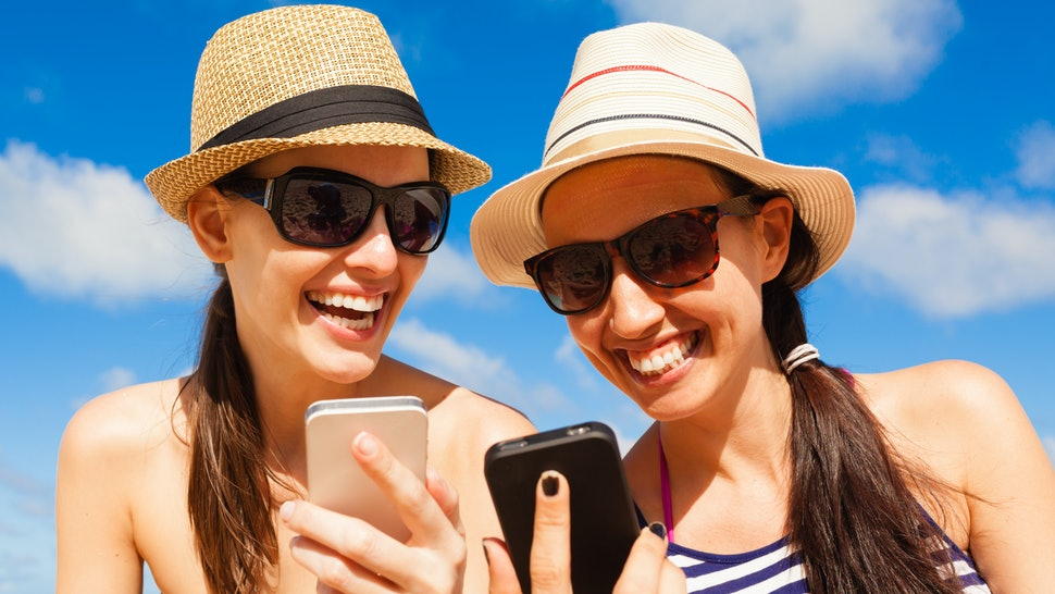 Pretty girls using smart phone on the beach. Summer holiday, technology and beach concept.