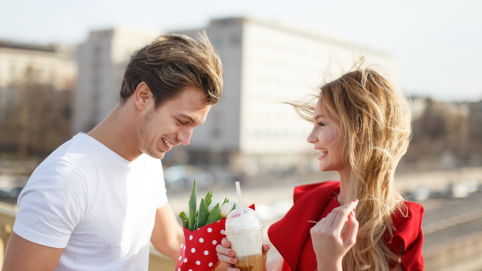 Young man give bouquet to woman in red dress at first date