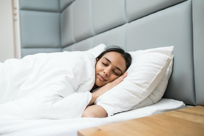 attractive woman sleeping on pillows under blanket in bed