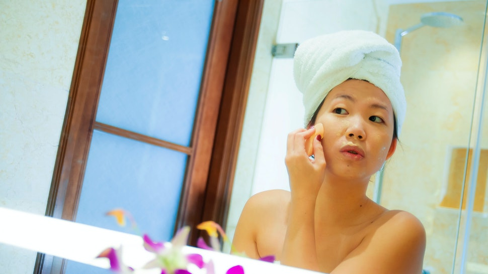 lifestyle fresh portrait of young happy and beautiful Asian Korean woman at home or hotel bathroom wrapped in toilet towel applying makeup cheerful and natural in female beauty and skin care