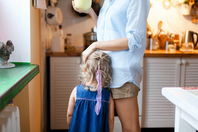 Mother is hugging kid. Mom comforts daughter in cozy kitchen. Woman is drinking tea. Child girl need...