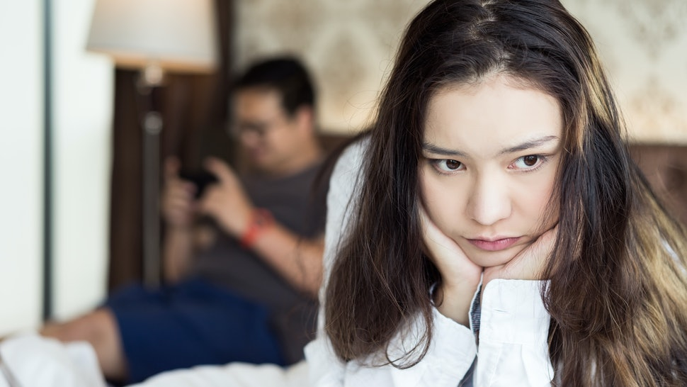 Pensive upset woman feeling offended, thinking over problems in relationships when her boyfriend playing game. Unhappy couple concept