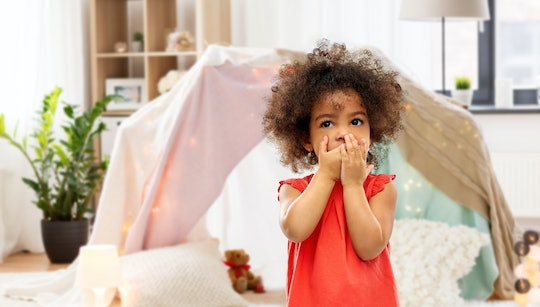 childhood, expressions and emotions concept - confused little african american girl covering mouth by hands over kids tent or teepee at home background