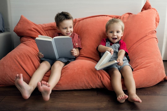 Two boys sit with books on a soft armchair. Family brothers read books positively.