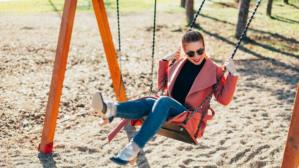 Young happy woman having fun on the swing in the playground