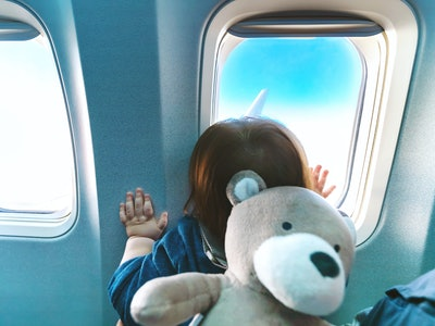 Little toddler boy looking out an airplane window while flying