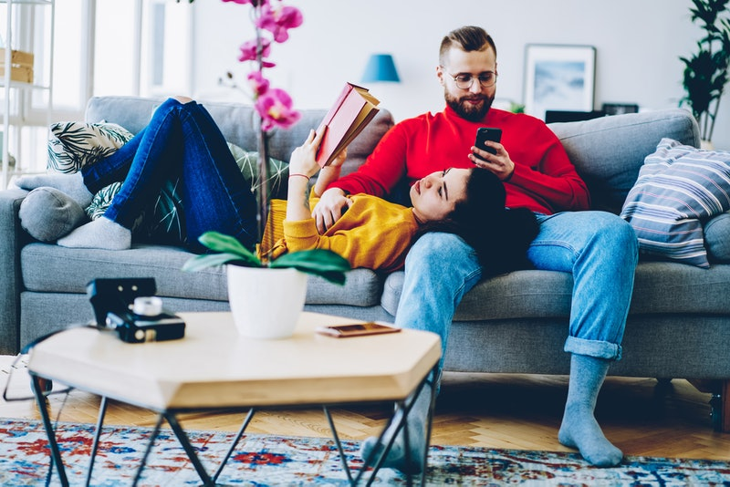 Concentrated man sending text message on smartphone using home wifi on leisure while his girlfriend ...