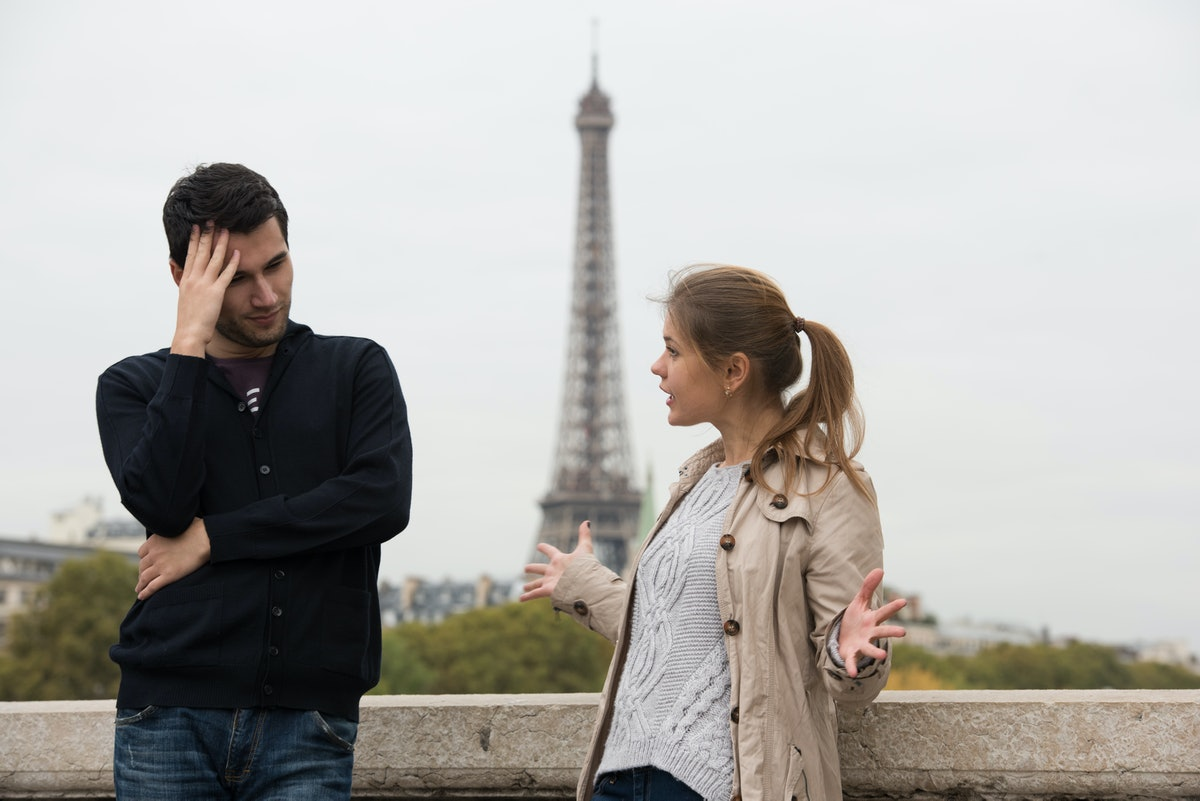 young couple man and woman standing on the bridge on river Seine, Paris, France, in front of Eiffel Tower, having fight