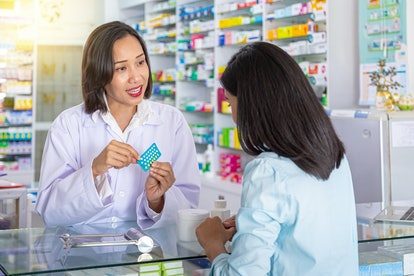 Female pharmacist counseling customer about contraceptive pill usage in modern pharmacy. Medicine, pharmaceutics, health care and people concept.