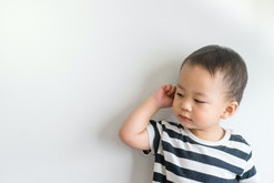Little baby boy has earache isolated on white background.2 years old baby boy hands touching in ear.