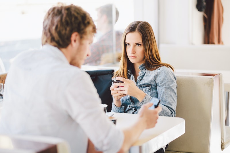 Young man talking on phone ignoring angry mad millennial girlfriend