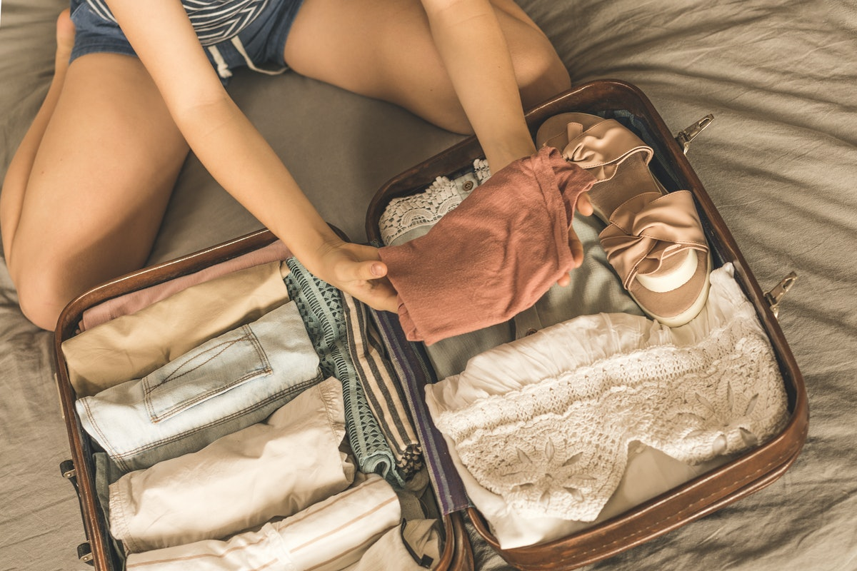 Summer travel and vacation concept. Young woman packing suitcase at home