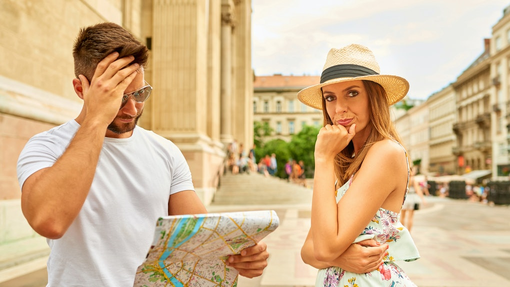 A beautiful young woman upset to her boyfriend who is looking at a map for a way at the St. Stephen's Basilica in Budapest, Hungary.