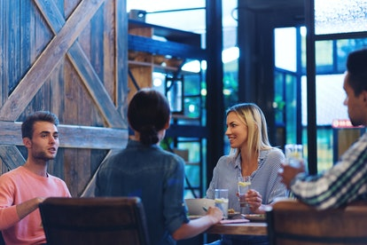 Four friends sitting at wooden table in restaurant and talking over dinner, young man telling story