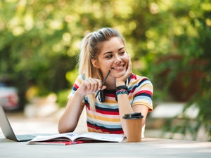 Image of a happy young cute girl student sitting in park using laptop computer writing notes.