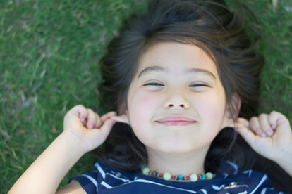little cute girl smiling pulling ears and lying on green grass